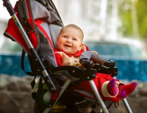 Smiling baby in sitting stroller on nature
